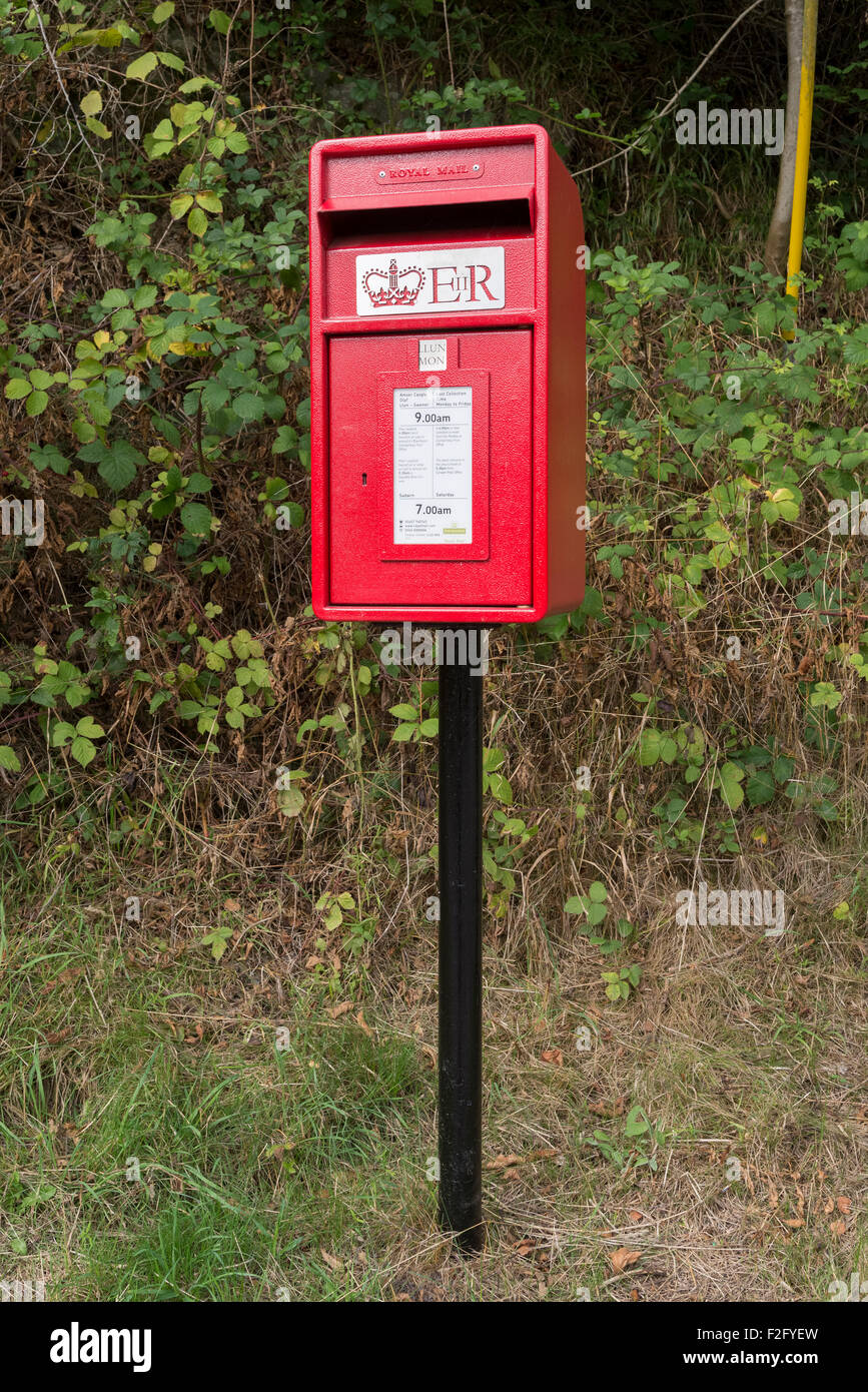 Modern country red postbox. - Stock Image