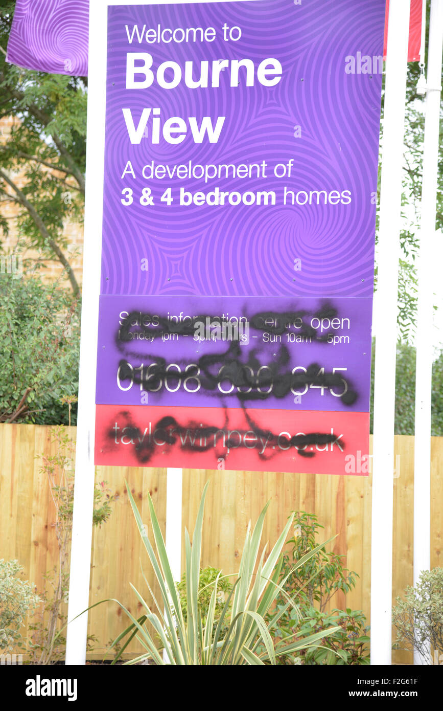 Defaced signs advertising a new housing development in the north Oxfordshire village of Hook Norton to which the - Stock Image