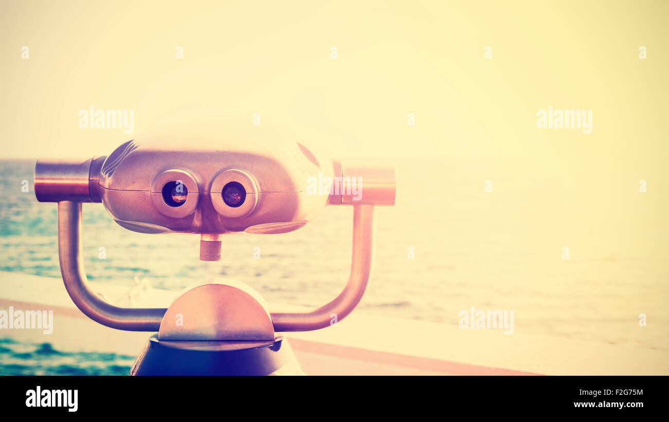 Vintage toned photo of a binocular pointed at horizon, future concept, copy space. - Stock Image