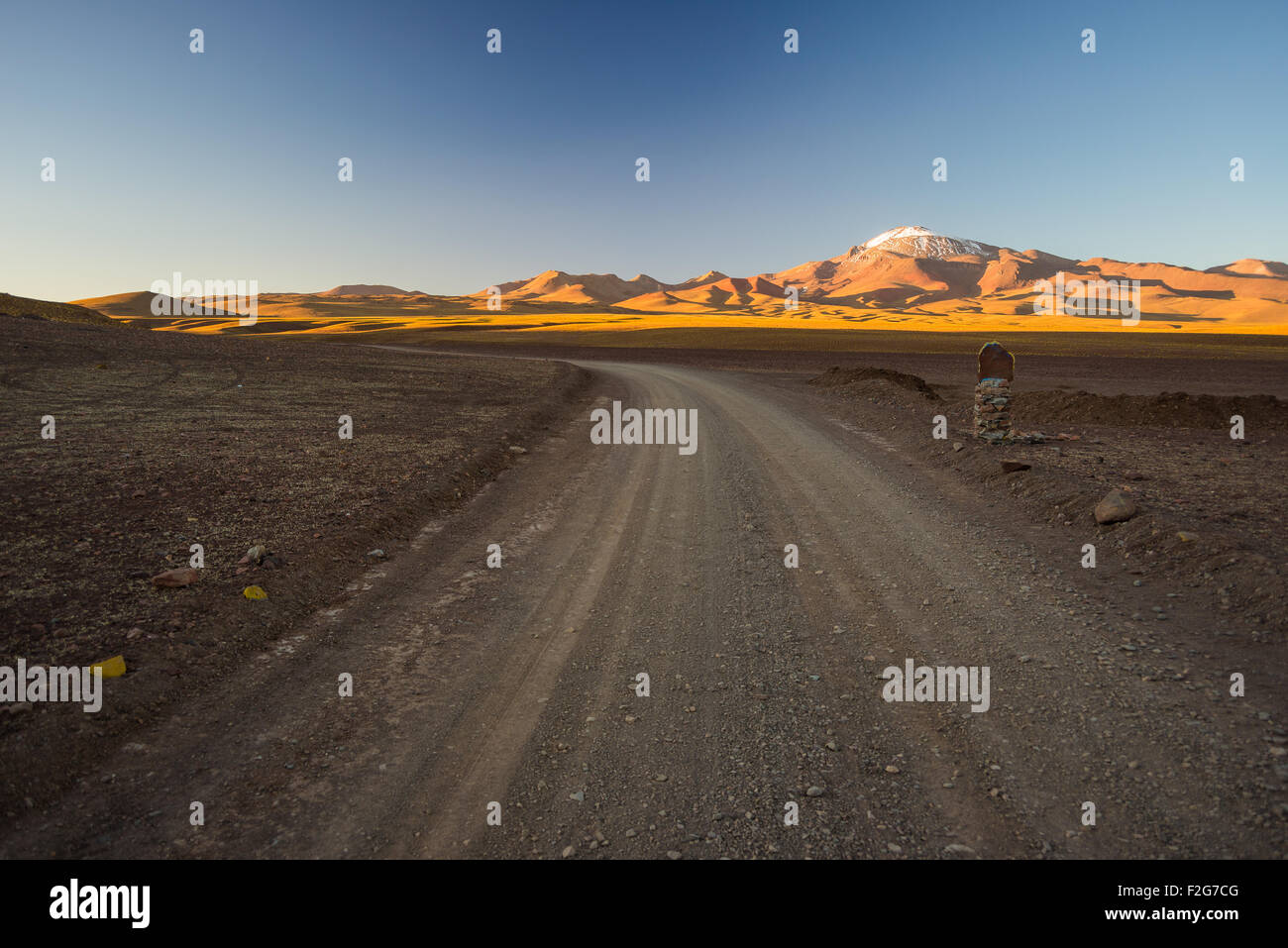 Empty dirt road on high altitude barren mountain range on the highlands of the Andes on the way to the famous Uyuni - Stock Image