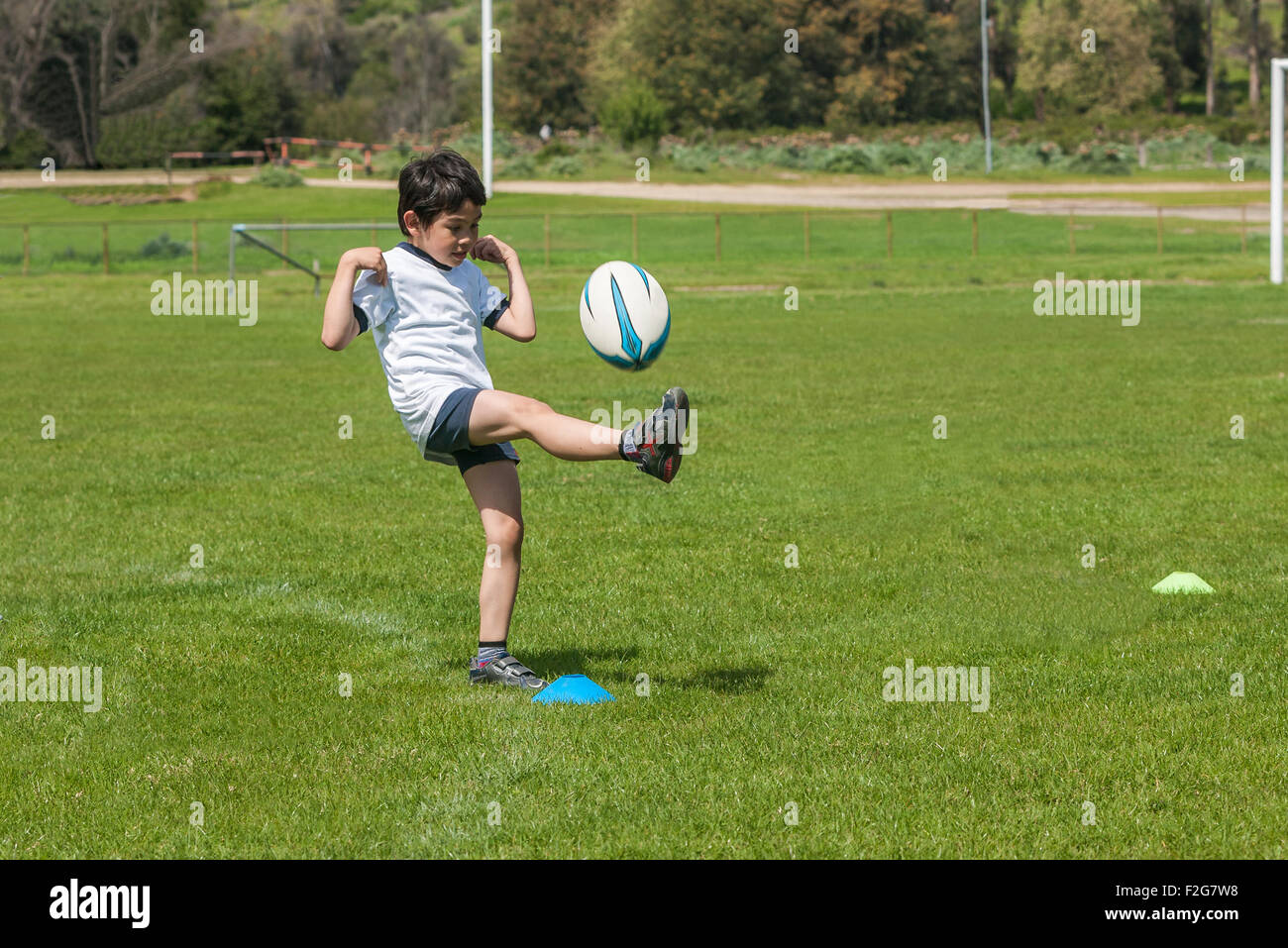 Rugbyman child shootig the ball Stock Photo