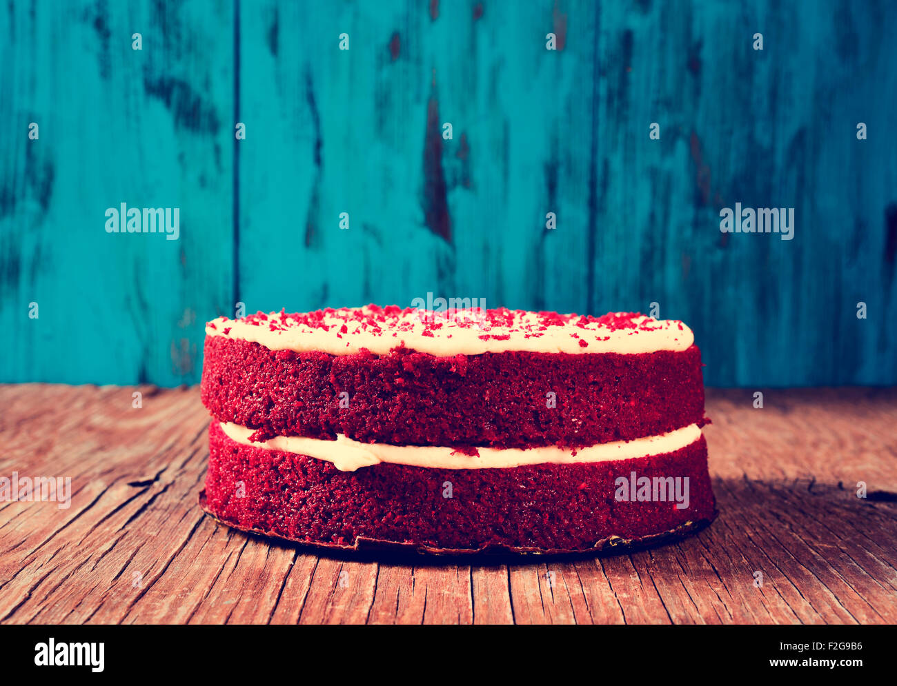 A Red Velvet Cake On Rustic Wooden Table And Blue Background With Filter Effect
