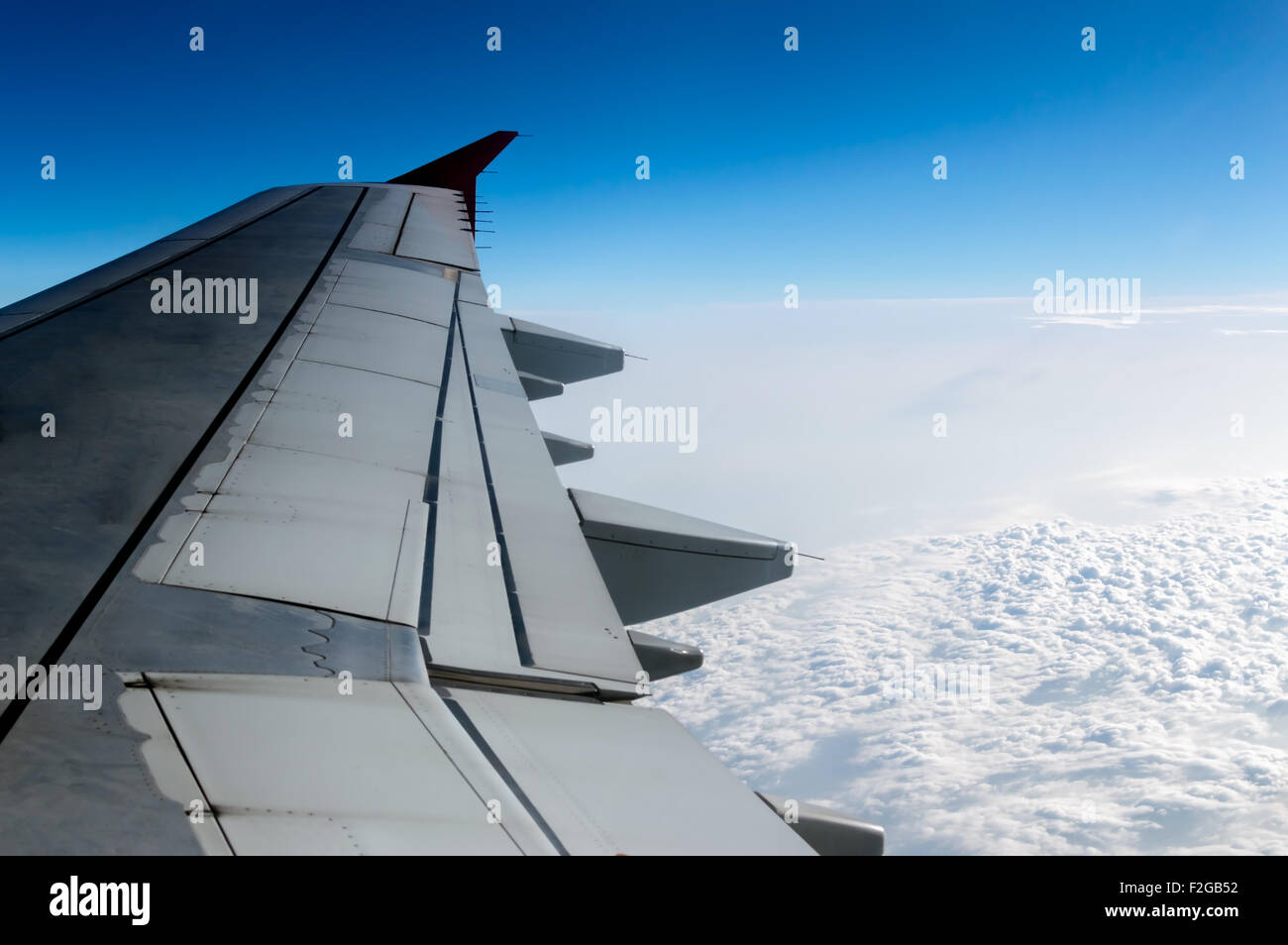 cloudy sky and airplane wing as seen through window of an aircraft. - Stock Image