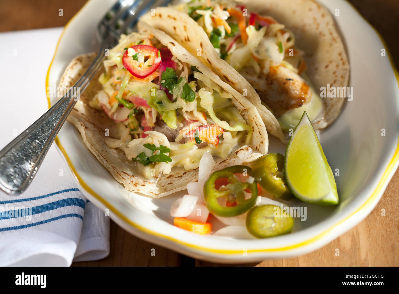 looking down at two fish tacos with spicy pickled cabbage, avocado and aioli on a plate with a fork and napkin - Stock Image