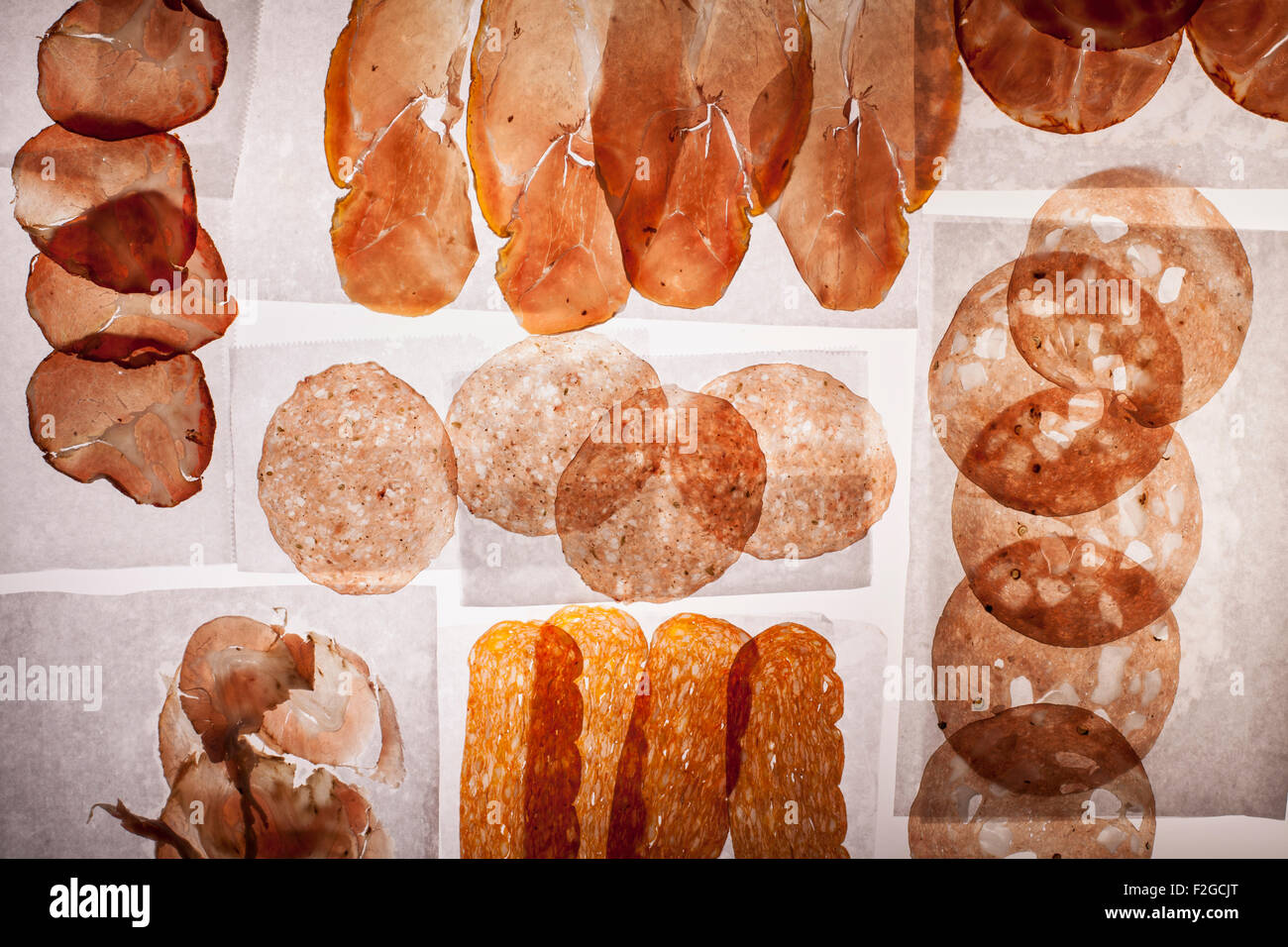 Translucent slices of various salami and prosciutto on white deli paper back lit on light table Stock Photo
