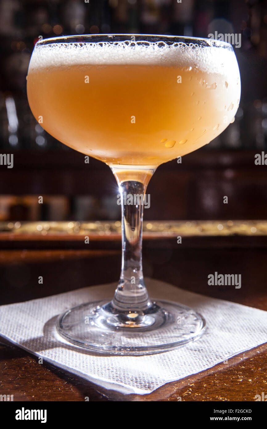 cocktail in bar, backlit, in coupe glass on napkin - Stock Image