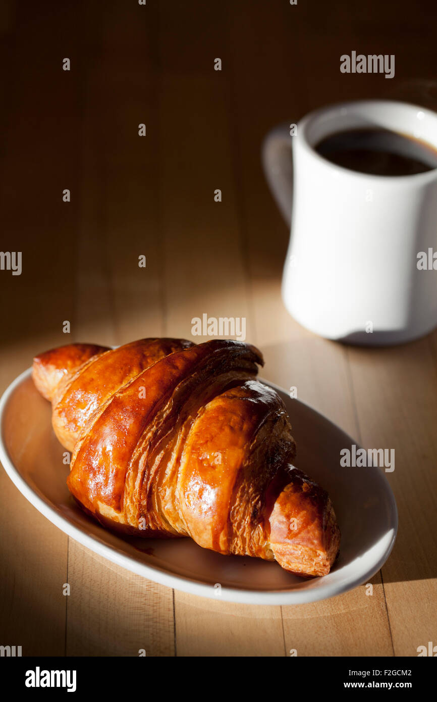 a brightly side lit croissant with a cup of coffee coming out of a shadow on a table - Stock Image