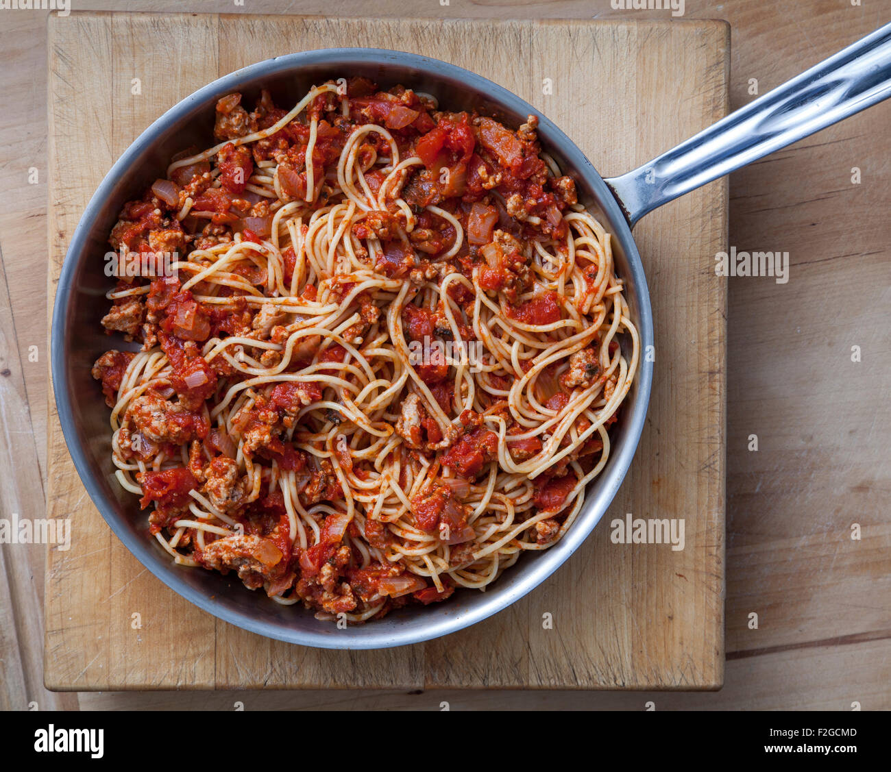 looking straight down on pasta bolognese in pan - Stock Image