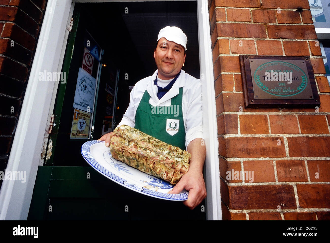Independent Lincolnshire butcher holding a plate of stuffed Chine. England. UK - Stock Image