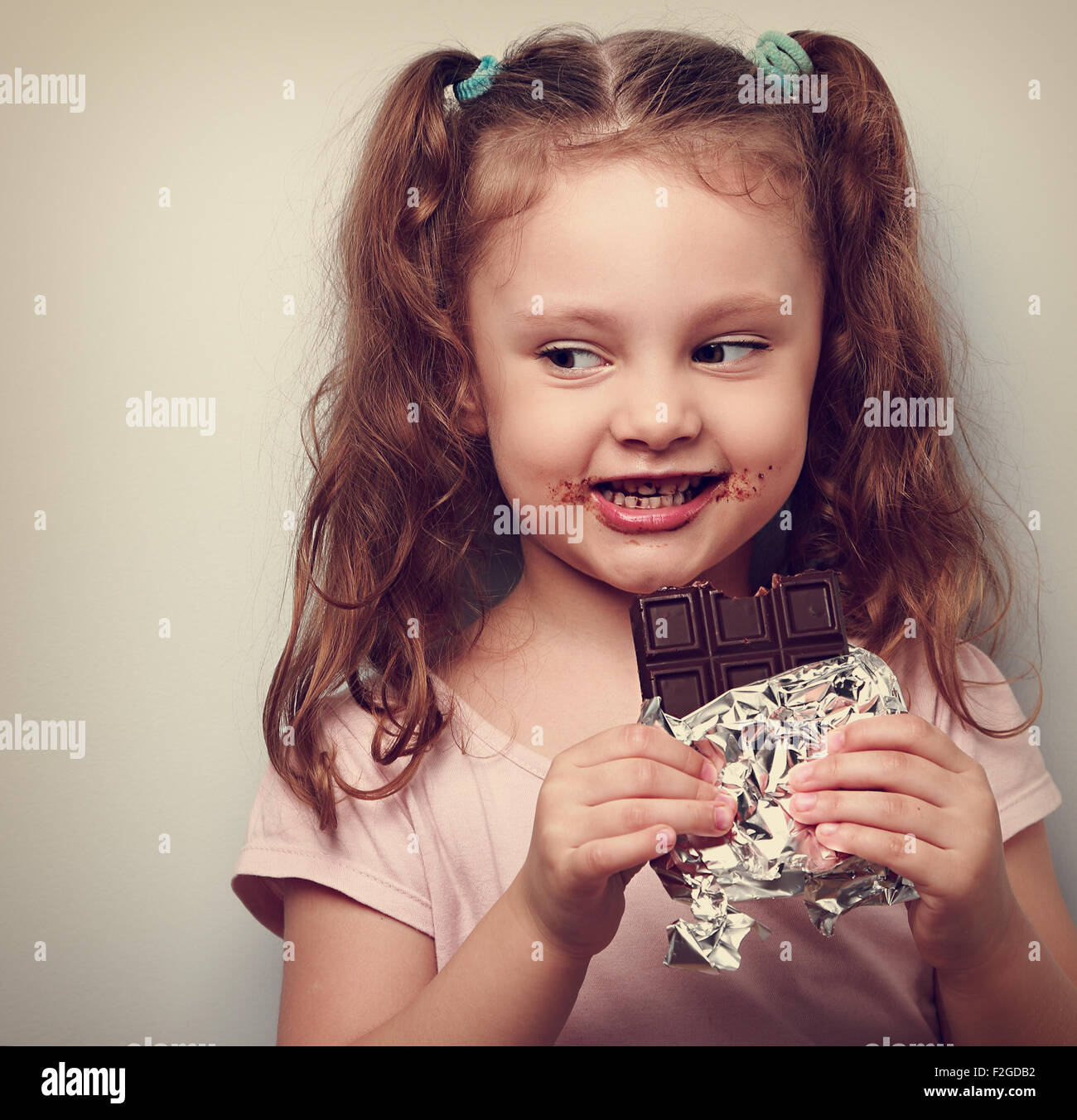 curious cute kid girl eating dark chocolate and looking fun. closeup