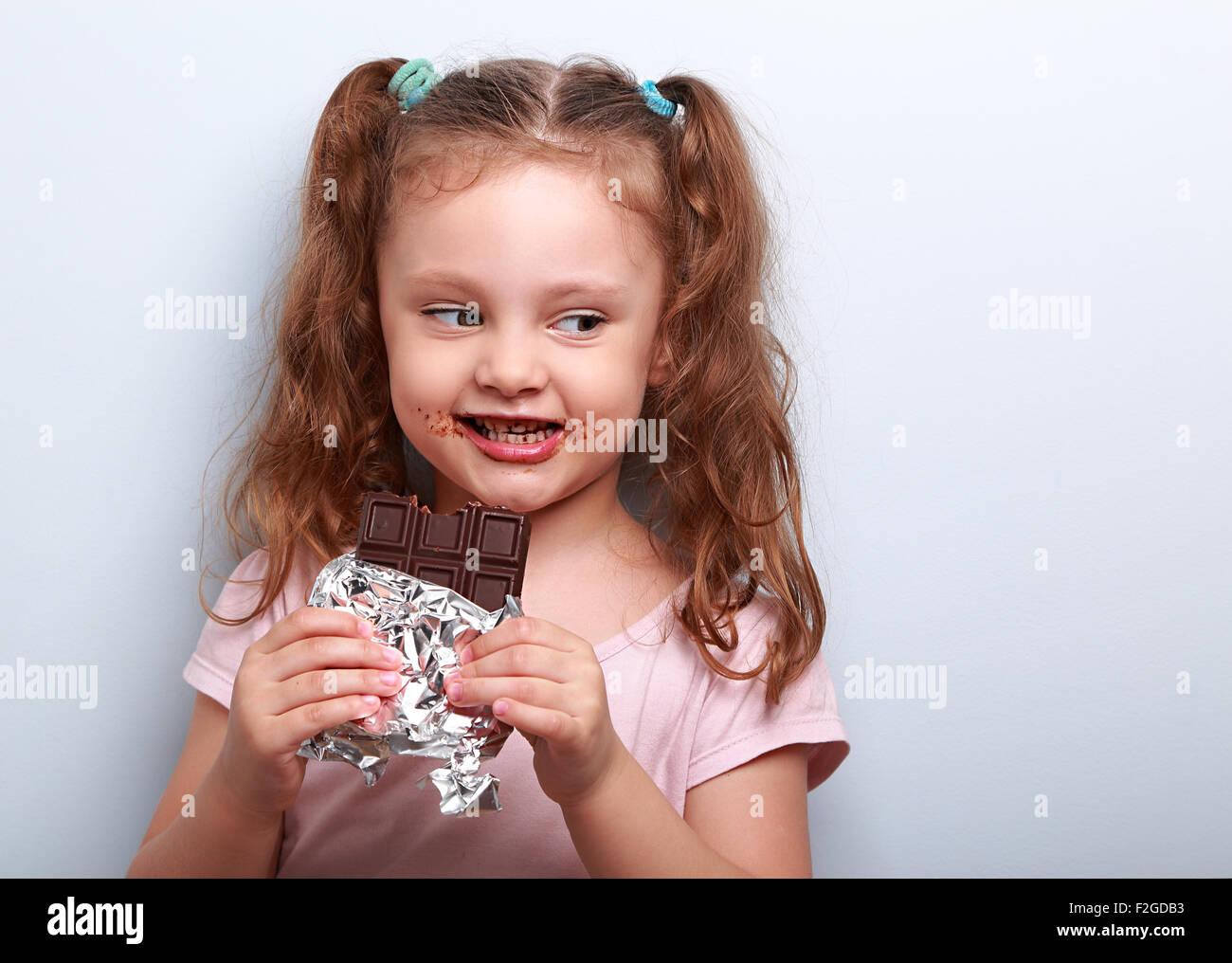 curious cute kid girl eating dark chocolate and looking fun. closeup