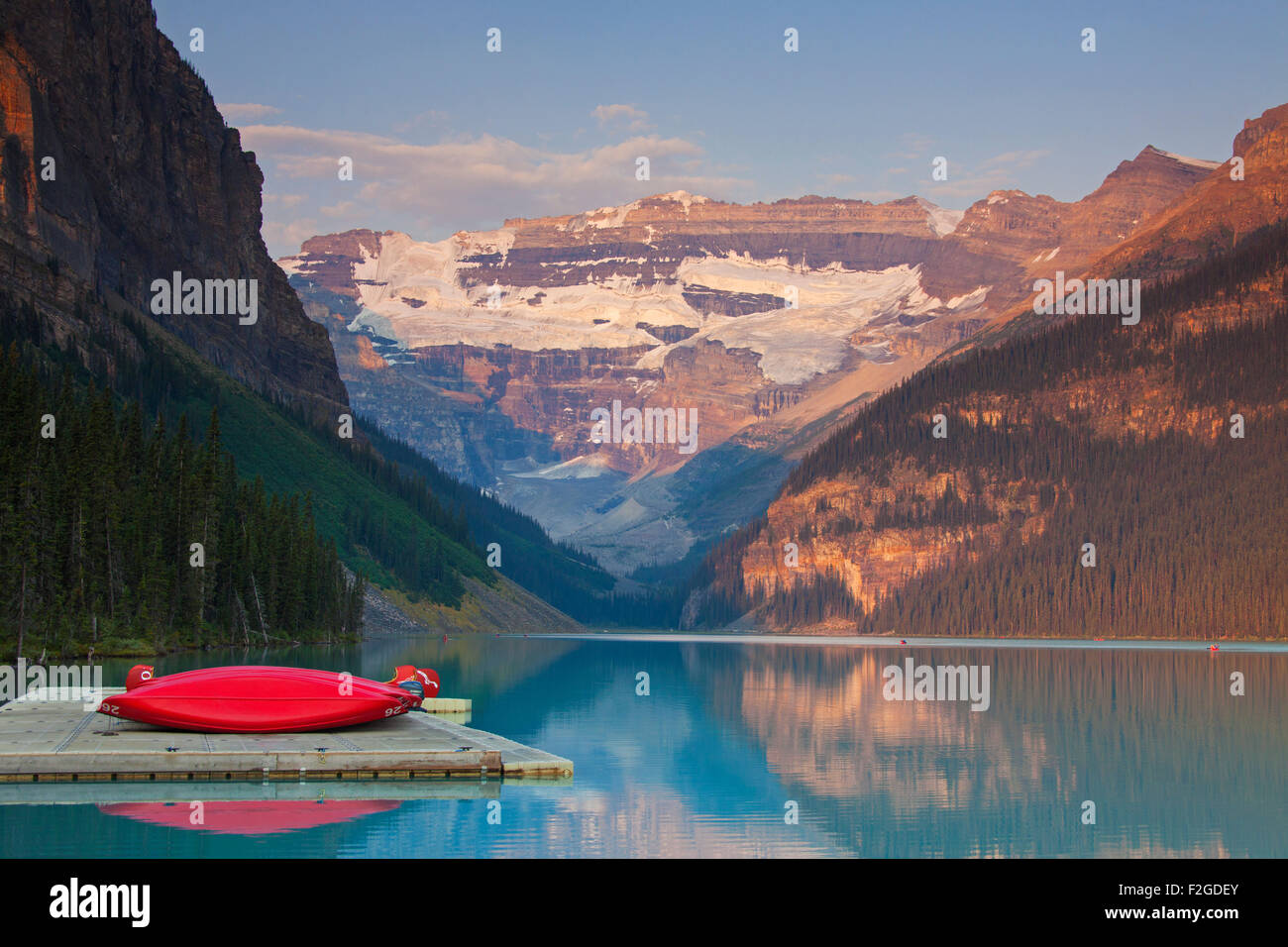 Red canoes at glacial Lake Louise with Victoria glacier, Banff National Park, Alberta, Canada - Stock Image