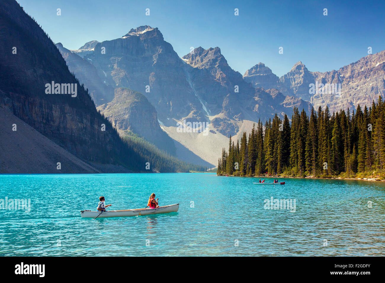 Tourists in canoe on Moraine Lake in the Valley of the Ten Peaks, Banff National Park, Alberta, Canada - Stock Image