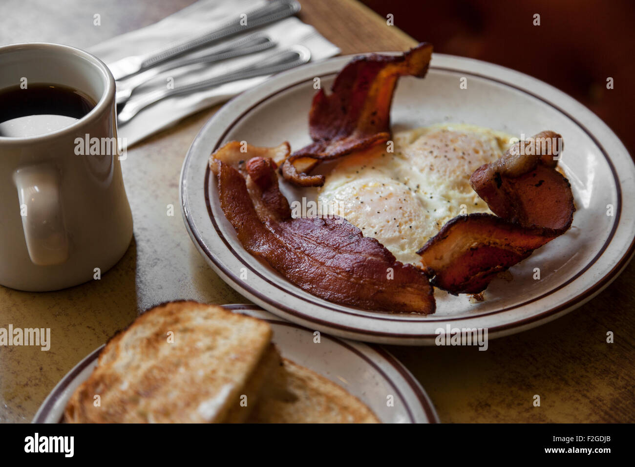 Eggs, bacon, toast and coffee at a diner with silverware - Stock Image