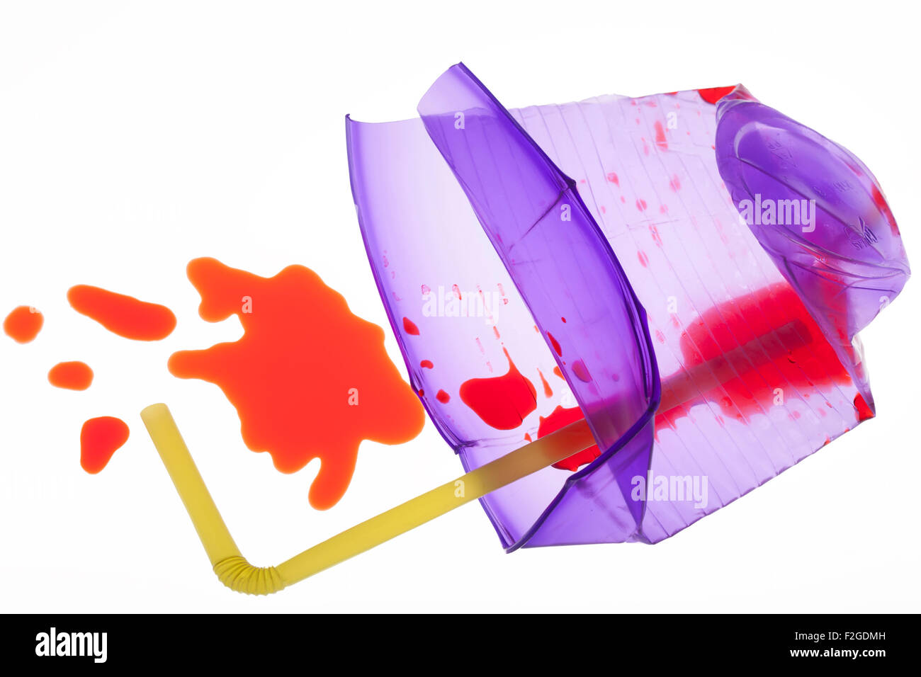smashed translucent purple cup with  yellow straw with red liquid spilling out on white light box - Stock Image