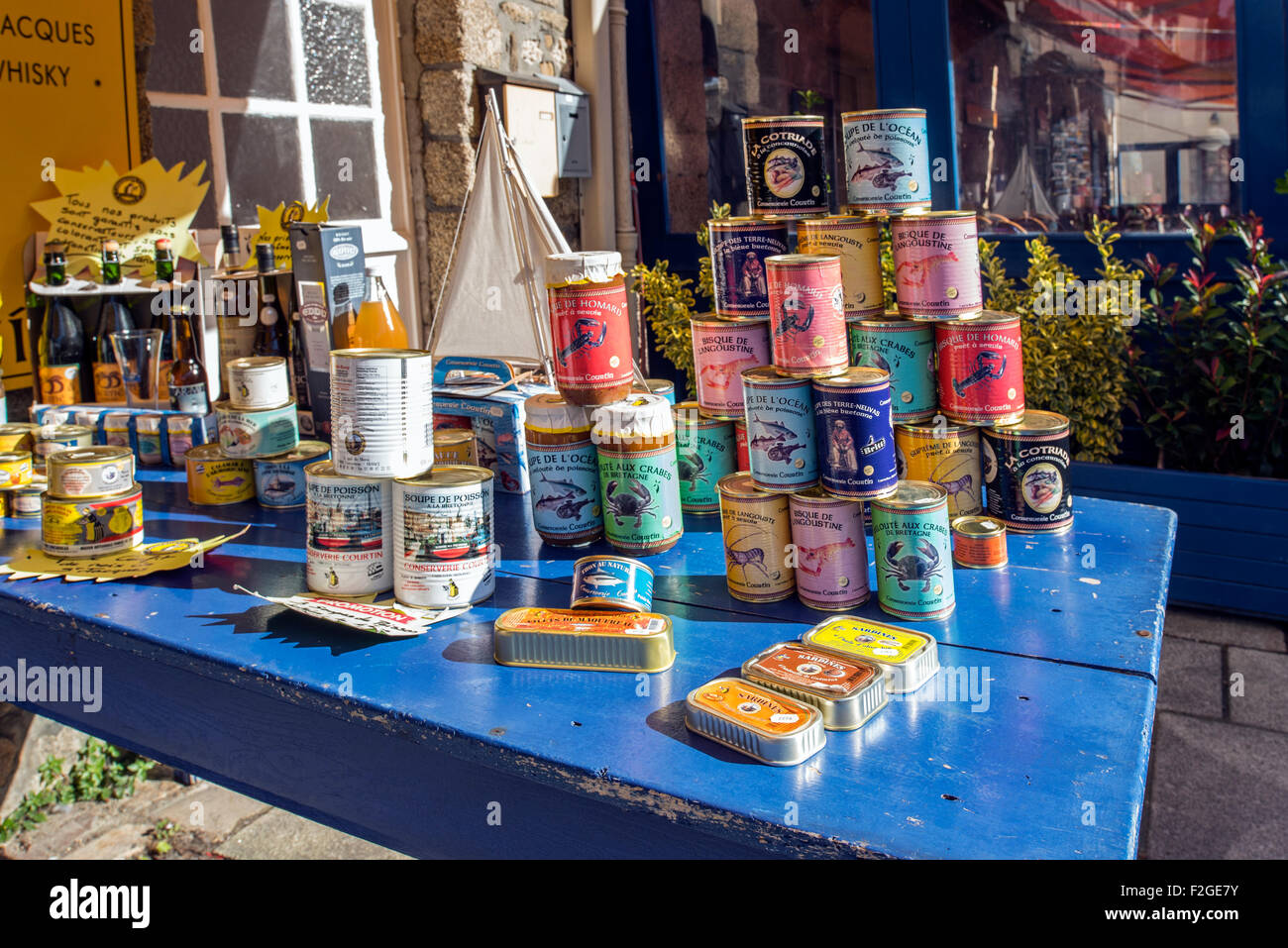 Tins of sardines and cans with crab and lobster meat in front of souvenir shop, Ville Close at Concarneau, Finistère, - Stock Image