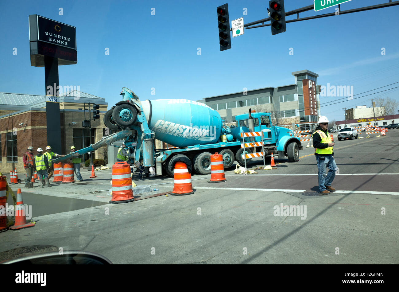 Workers using concrete from Chemstone rotating cement truck to build city street. St Paul Minnesota MN USA - Stock Image