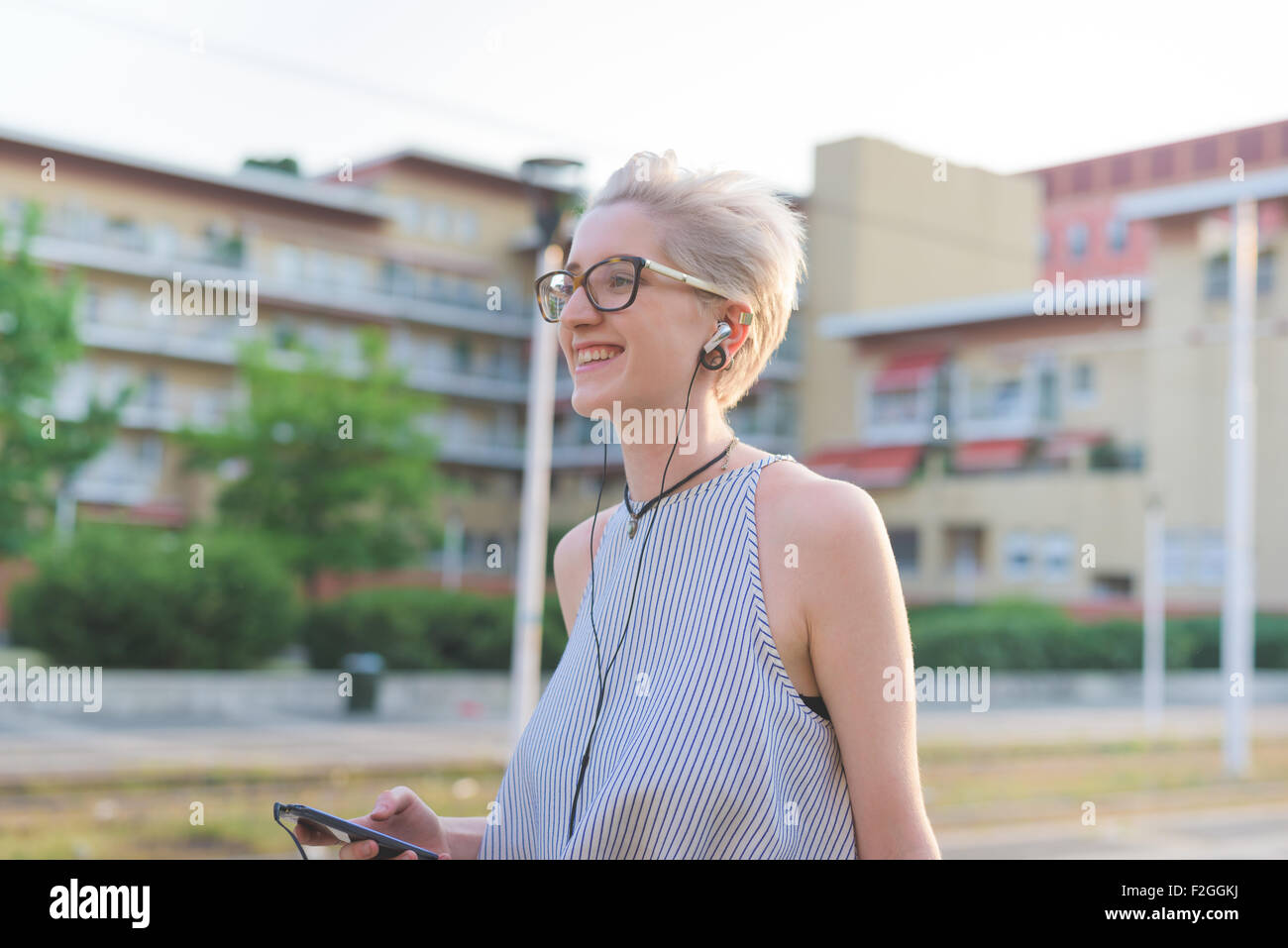 half length of young handsome caucasian blonde designer listening music with earphones, overlooking right, smiling - Stock Image
