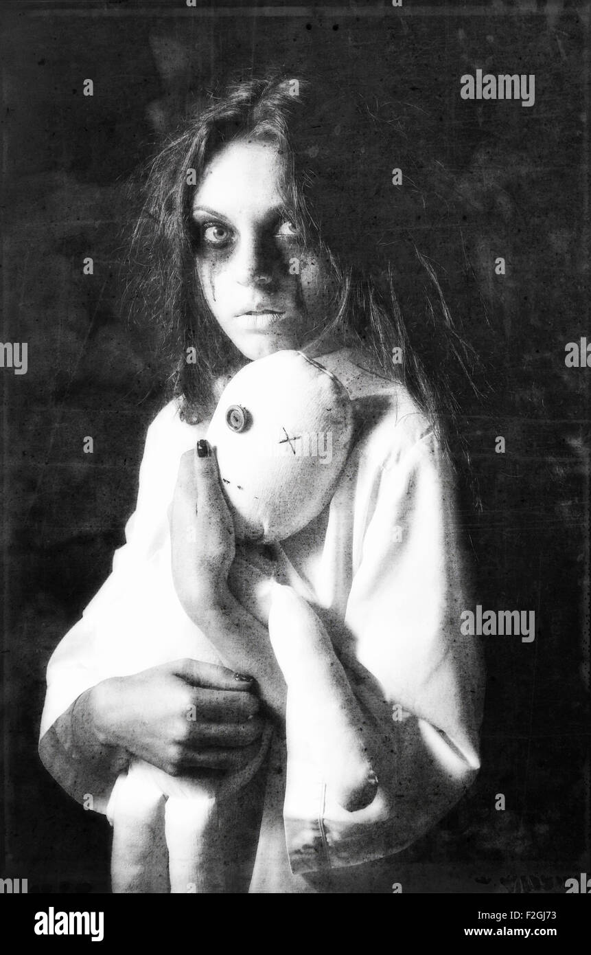 Horror style shot: the mysterious ghost girl with moppet doll in hands. Grunge texture effect - Stock Image
