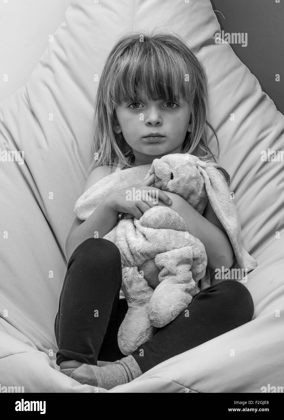Unhappy little girl cuddling a toy rabbit. - Stock Image