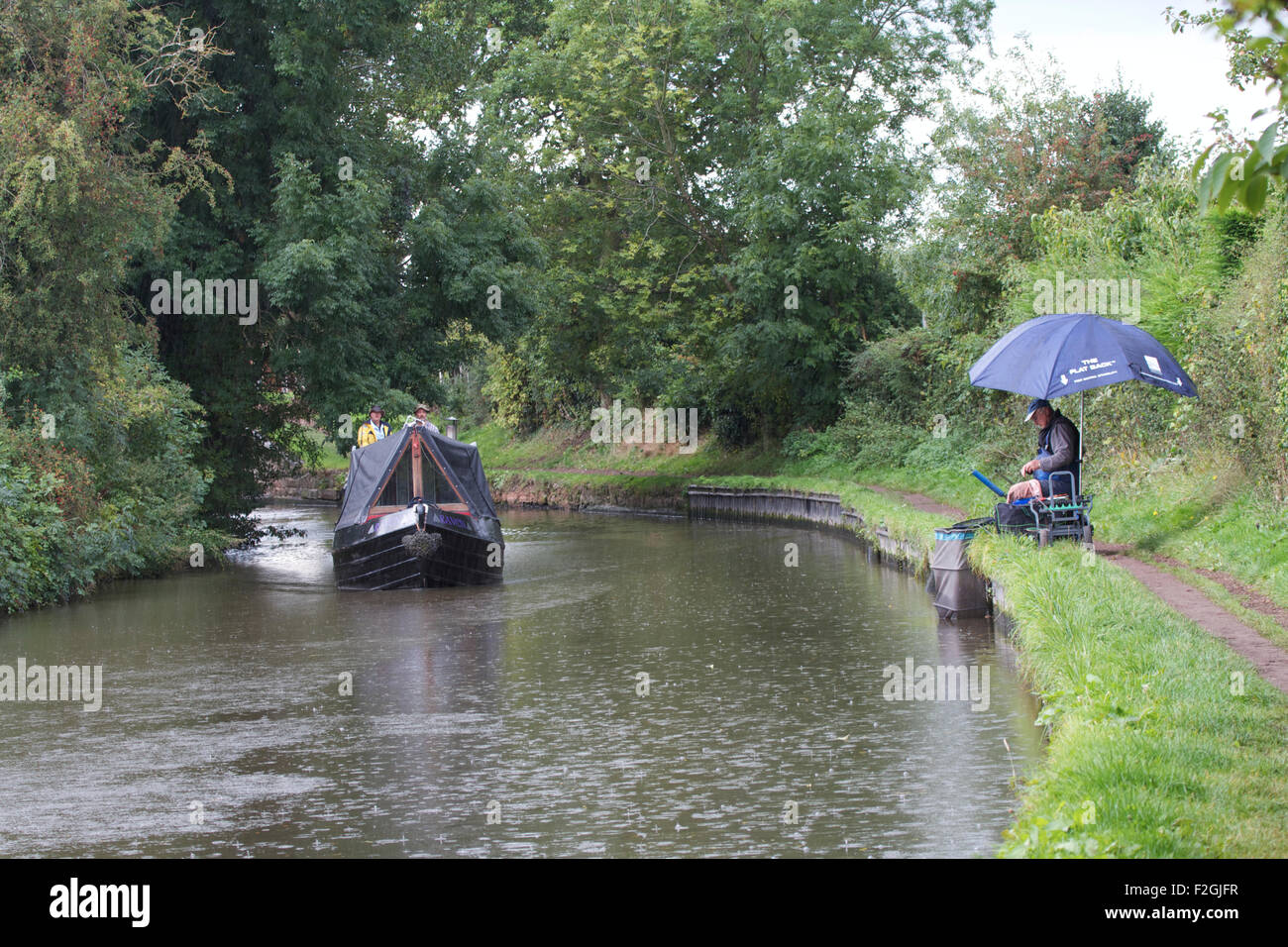 Barge and fisherman along the Staffordshire and Worcestershire Canal near Penkridge. UK Stock Photo