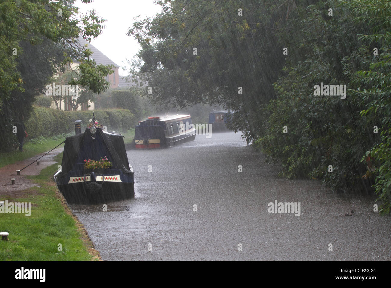 Boats moored on the Staffordshire and Worcestershire Canal at Penkridge, in heavy rain. UK - Stock Image