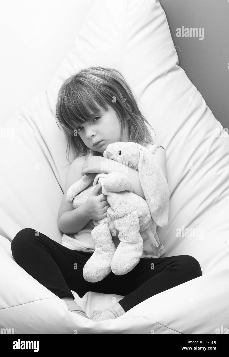 Angry child holding a soft rabbit - Stock Image