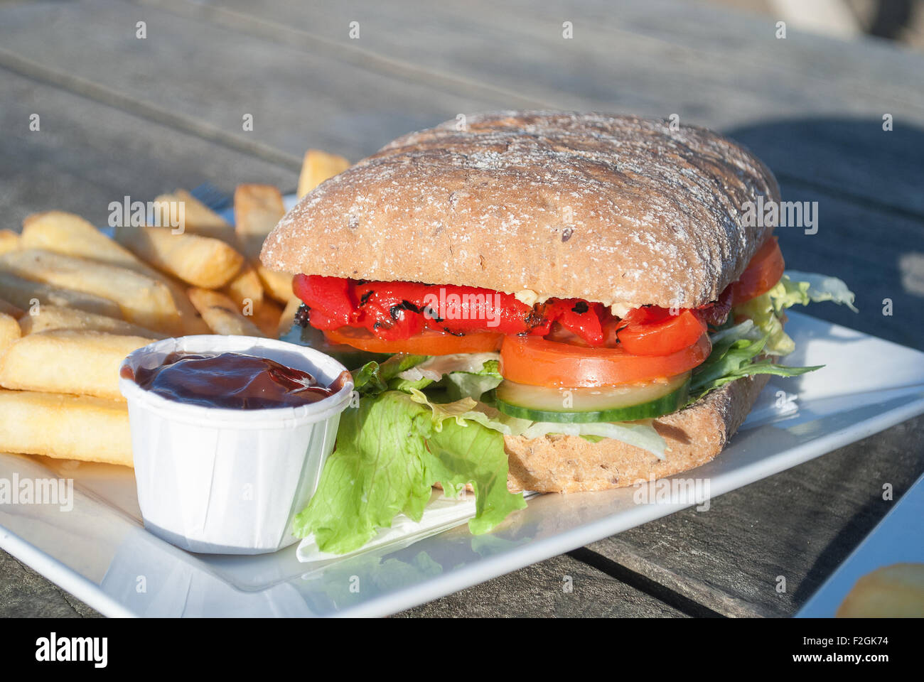 Vegan Roasted Pepper and Mixed Salad Sandwich, with chips and tomato sauce. - Stock Image
