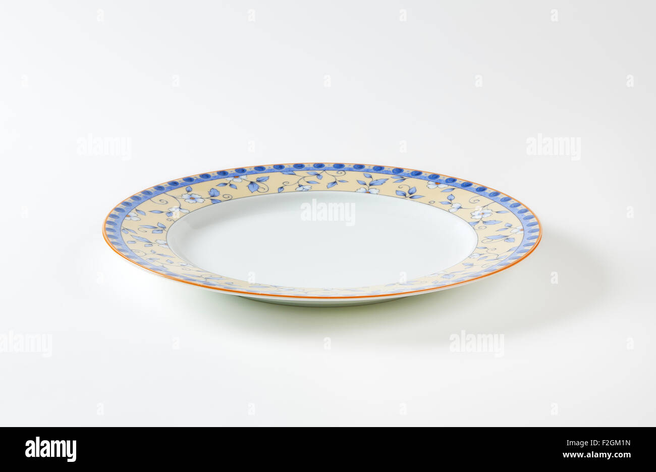 Country style dinner plate with floral design border and brown trim - Stock Image