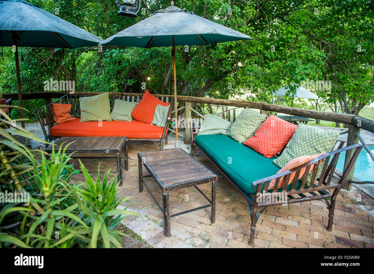 Outdoor patio with colorful cushioned couches in Botswana, Africa - Stock Image