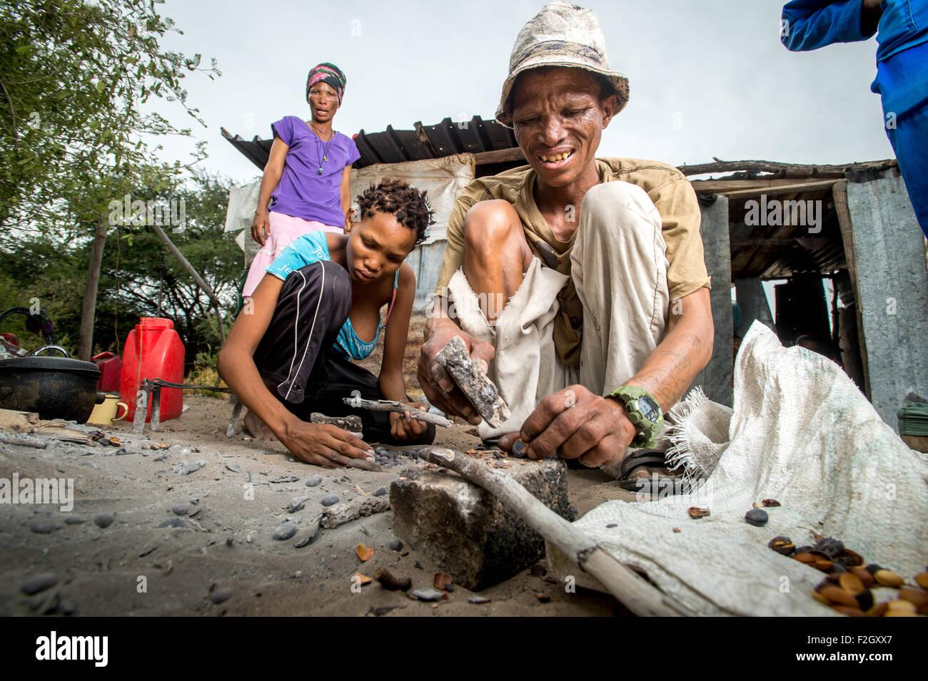 Bushmen or San people preparing food in Botswana, Africa - Stock Image