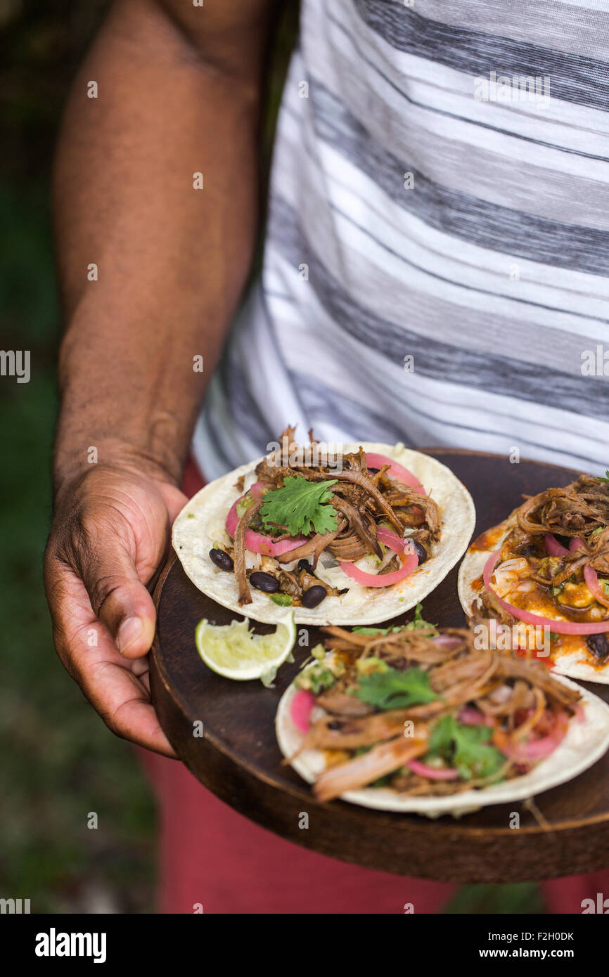 A man is getting ready to serve slow-cooked beef brisket tacos served on a wooden plate outdoors. - Stock Image