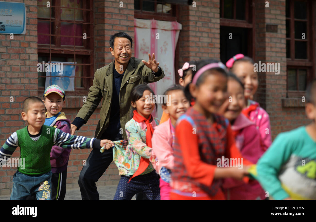 (150919) -- QIN'AN, Sept. 19, 2015 (Xinhua) -- Teacher Li Anxi plays with students at Shanwang Primary School - Stock Image