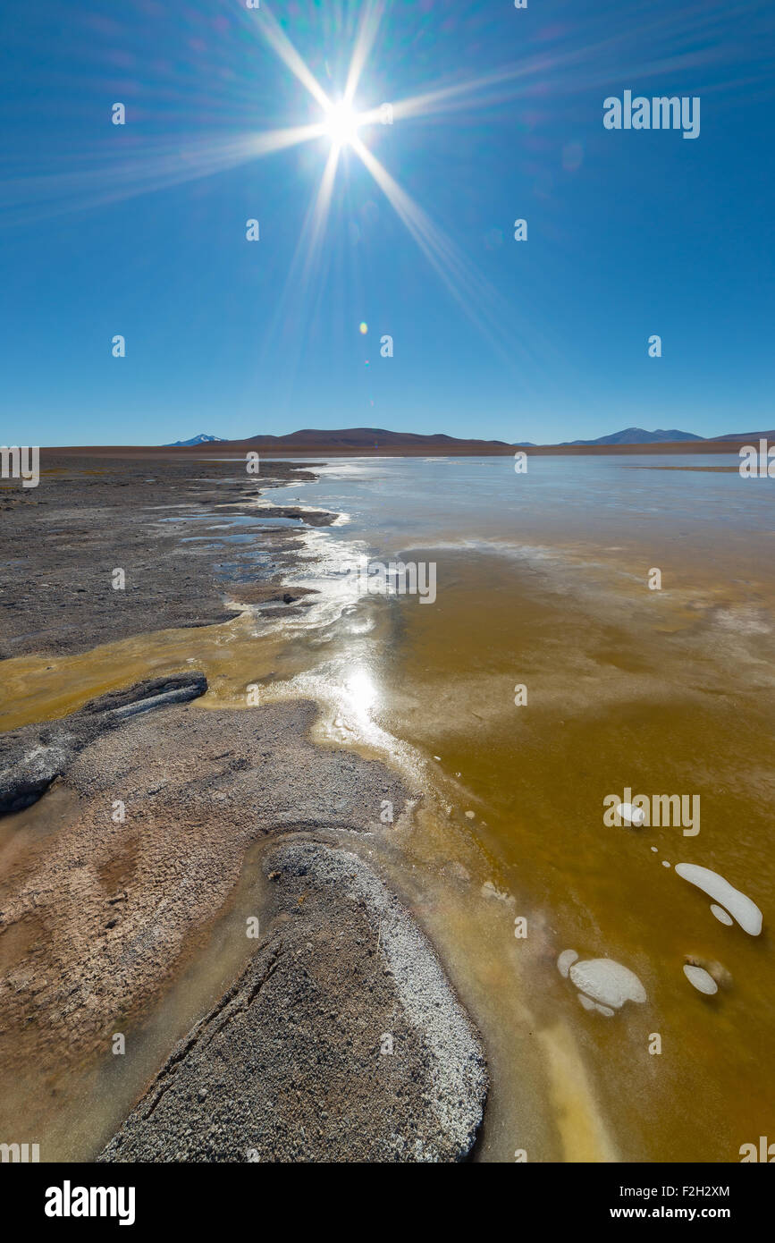 Wide angle view of a frozen salt lake ('Laguna Helionda') on the way to the famous Uyuni Salt Flat, among - Stock Image