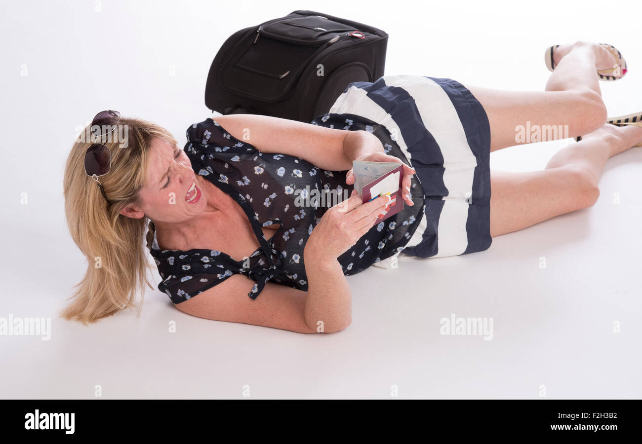 Angry delayed airline passenger laying on the floor with passport and bag Stock Photo