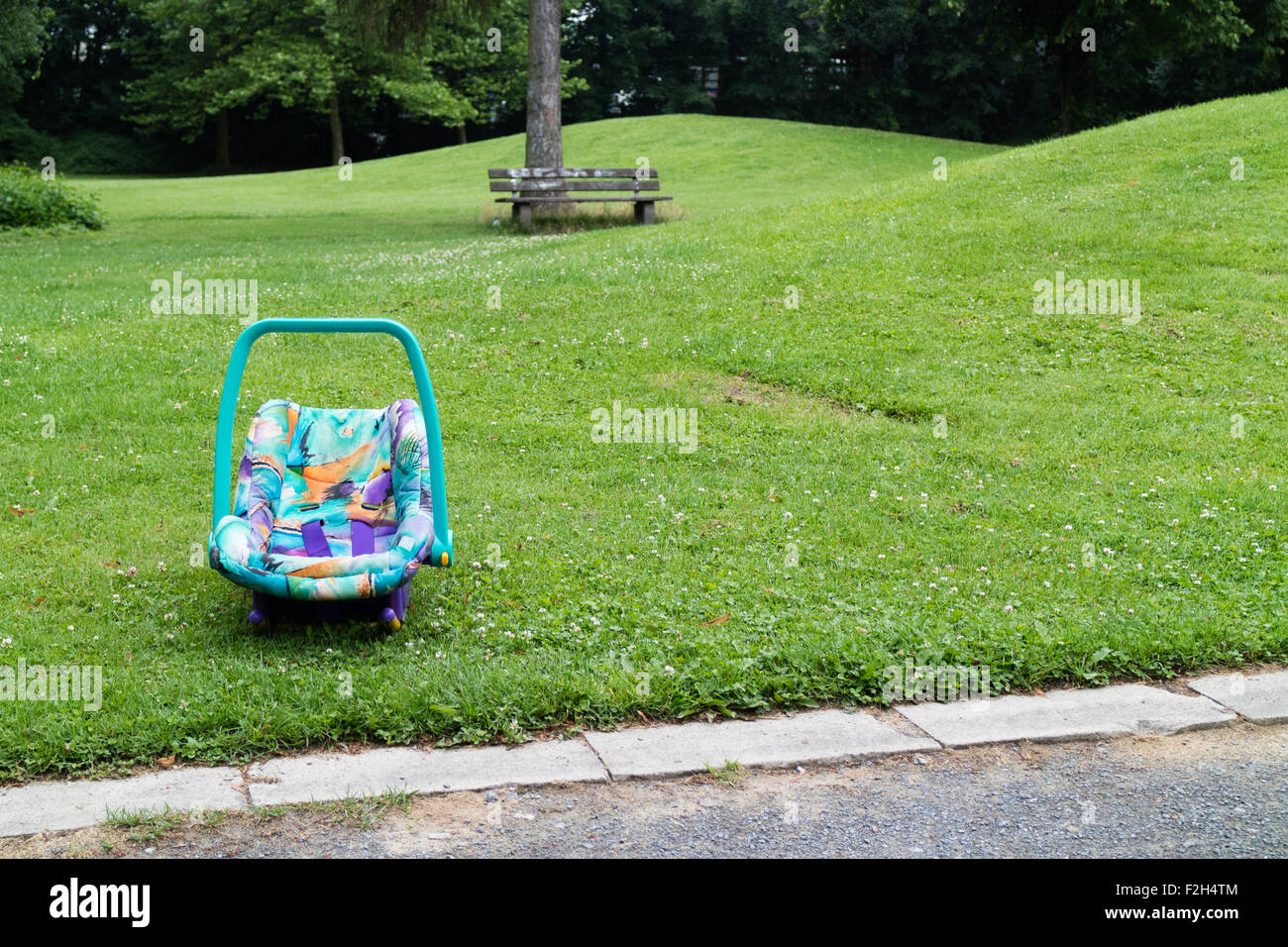 An abandoned baby's car seat in a park - Stock Image