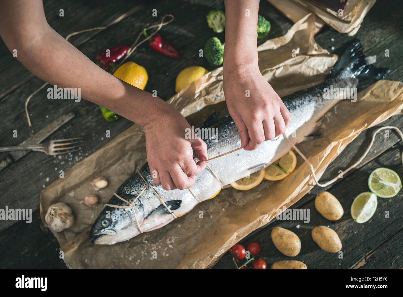 Tying a rope on fish for grilling. Baking paper - Stock Image