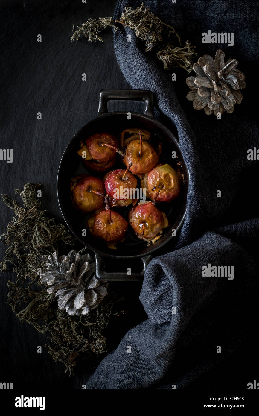 Roast apples in cocotte on slate background with kitchen towel and