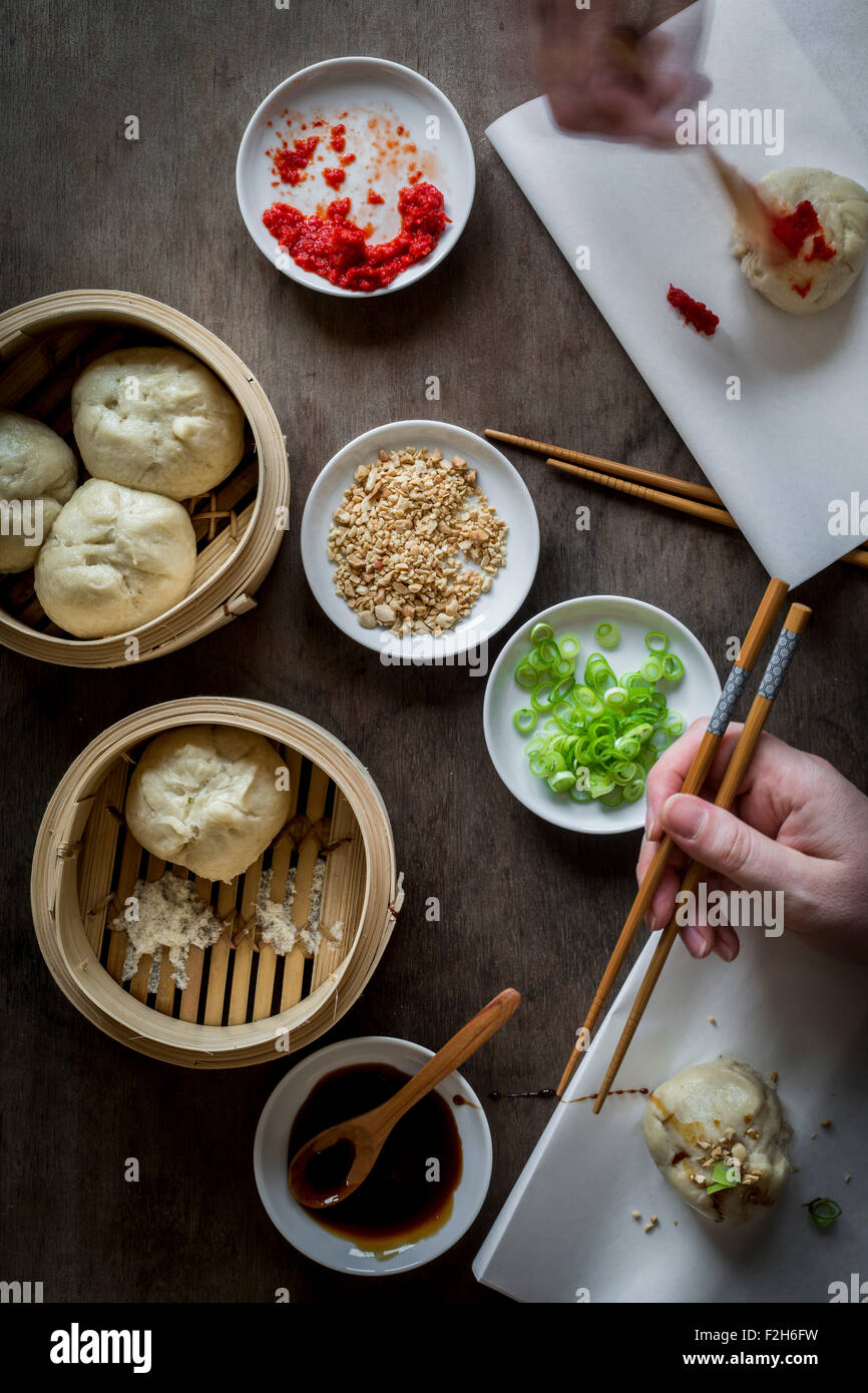 Two hands eating Asian street food with chopsticks on wooden tabletop with bamboo steamers. Top view Stock Photo
