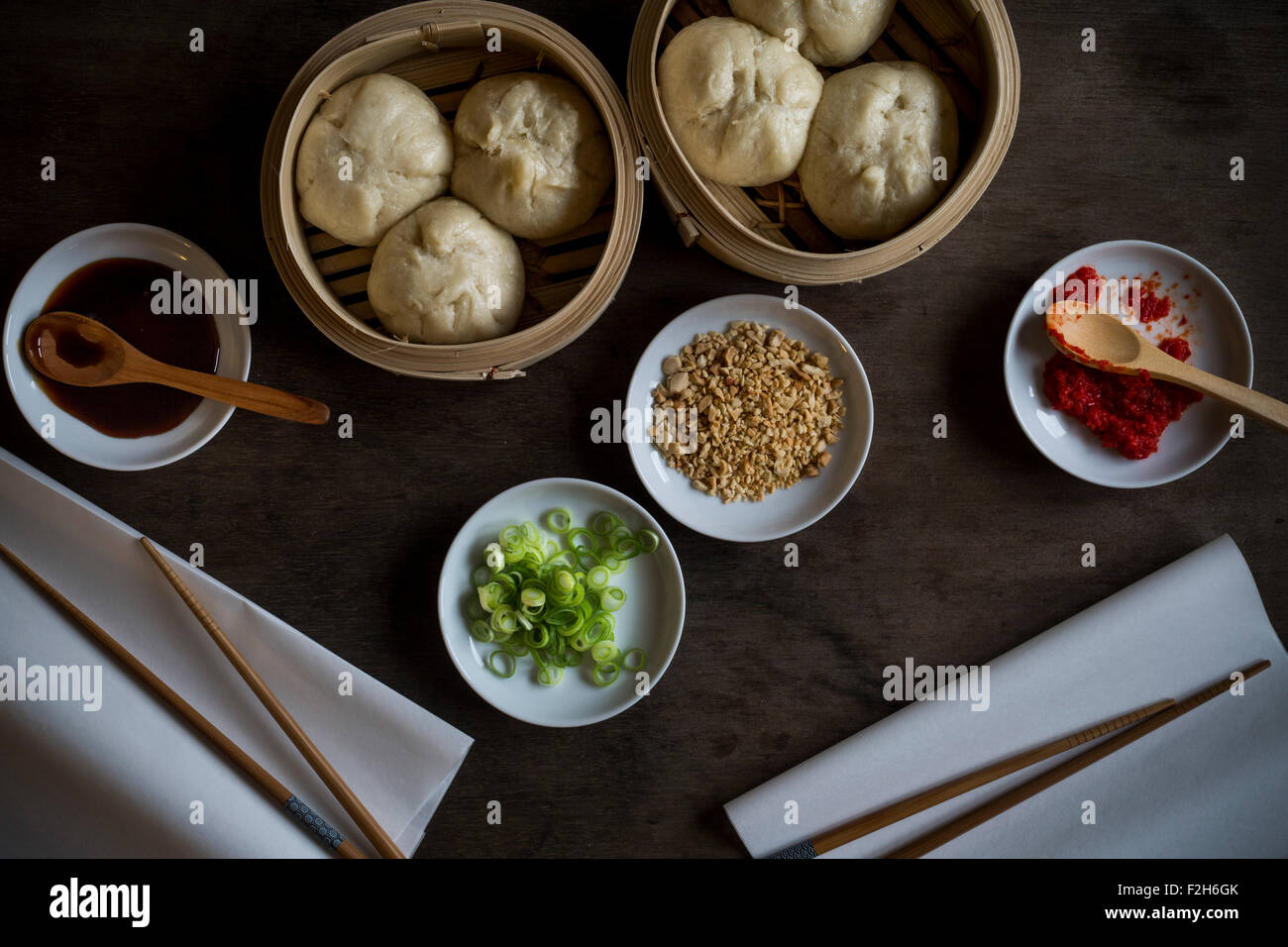Asian street food in bamboo steamers on wooden tabletop. Top view. - Stock Image