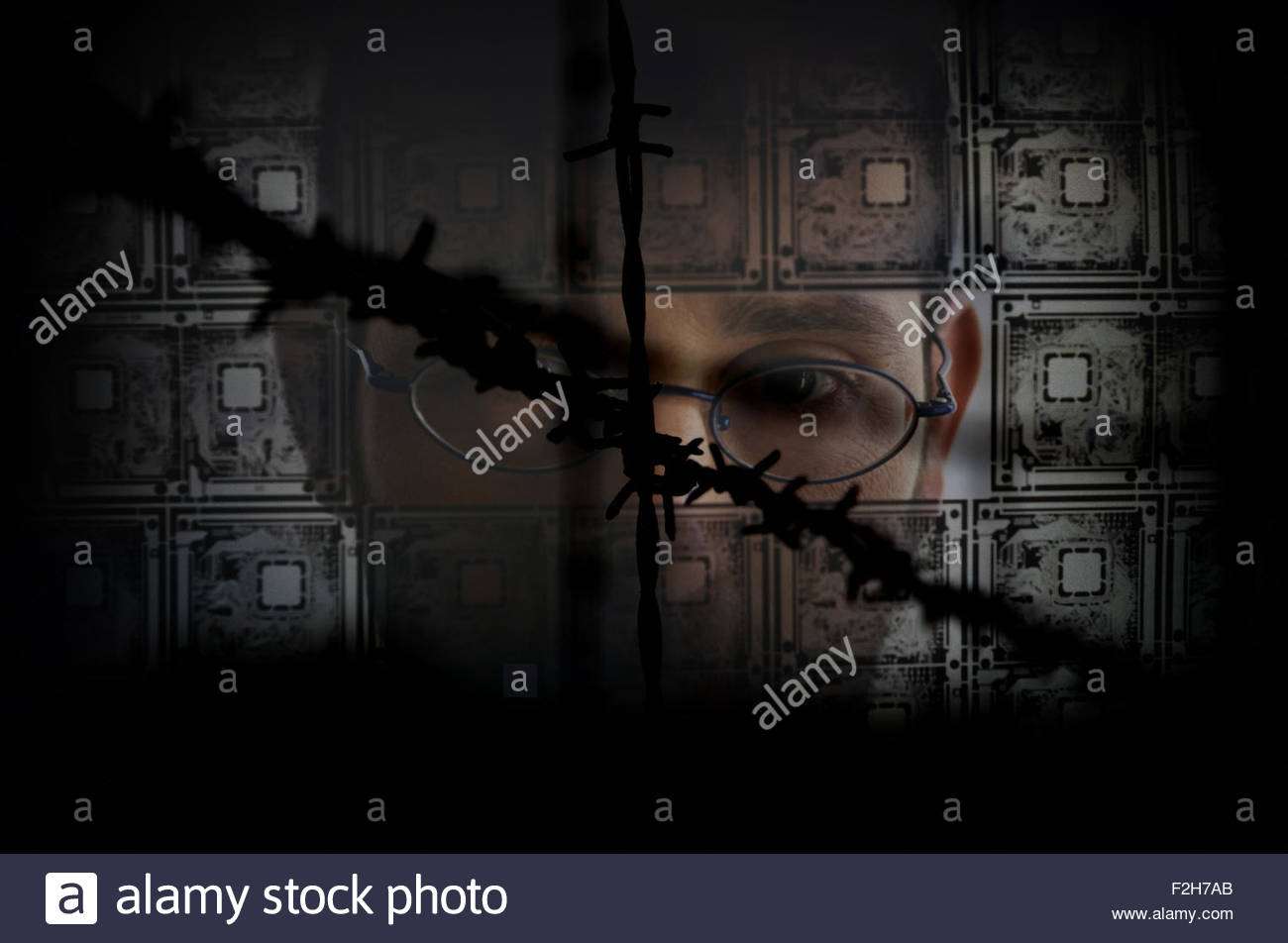 A person looking through transparent electric circuit board and barbed wire Stock Photo