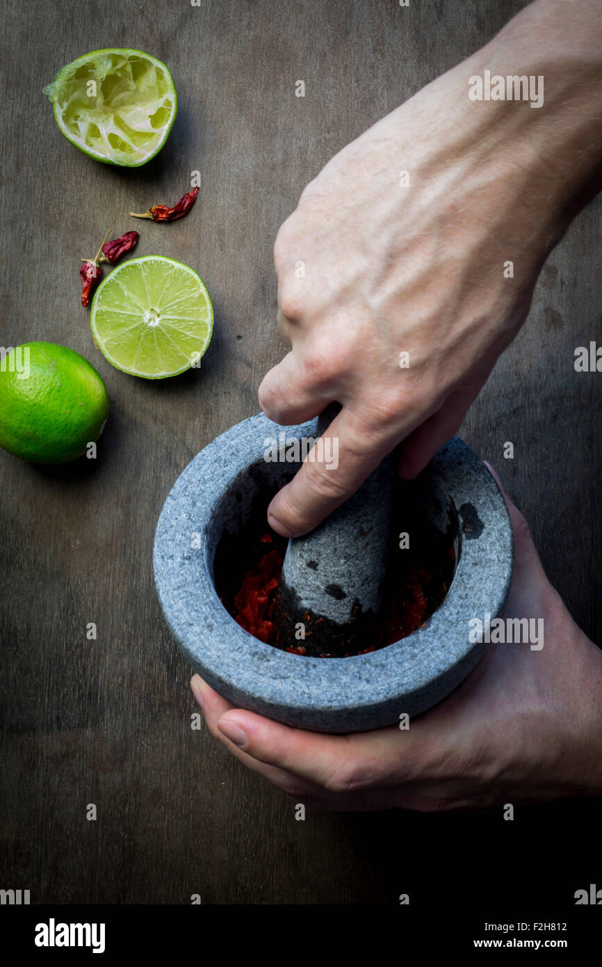 Man's hand with mortar and pestle preparing seasoning paste. Top view - Stock Image