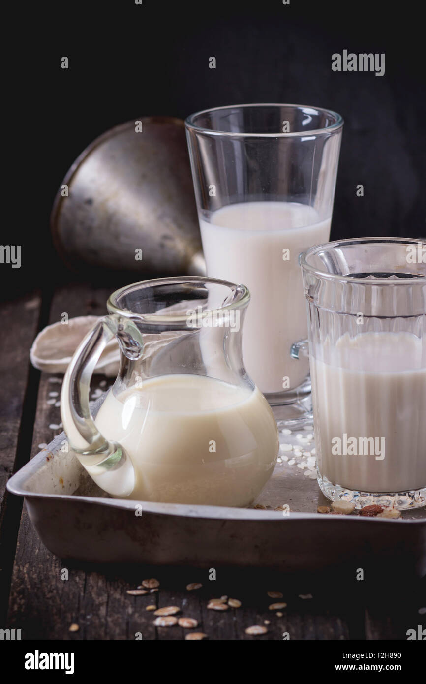 Set of non-dairy milk (rice milk, almond milk and oat milk) in glass cups and jug on old aluminum tray with rice - Stock Image