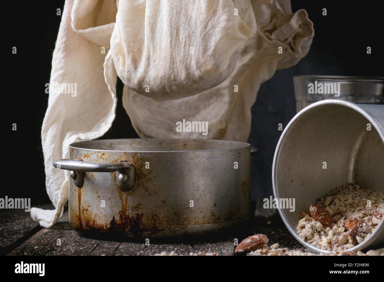 Process of making non-dairy almond milk - extraction of grain almond via white textile at vintage pan over old wooden - Stock Image