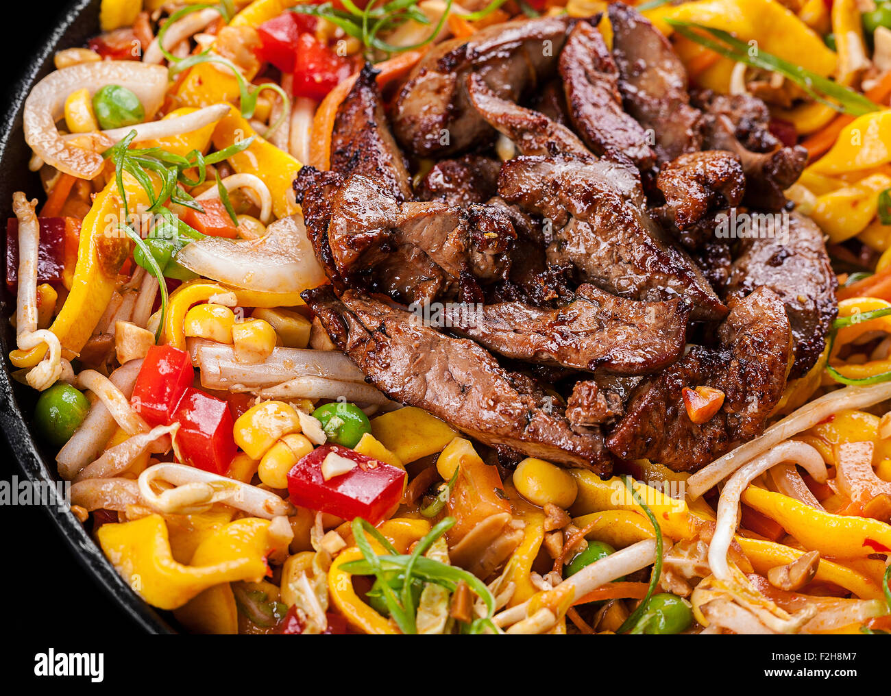 Fried chicken liver with egg noodle and vegetable - Stock Image