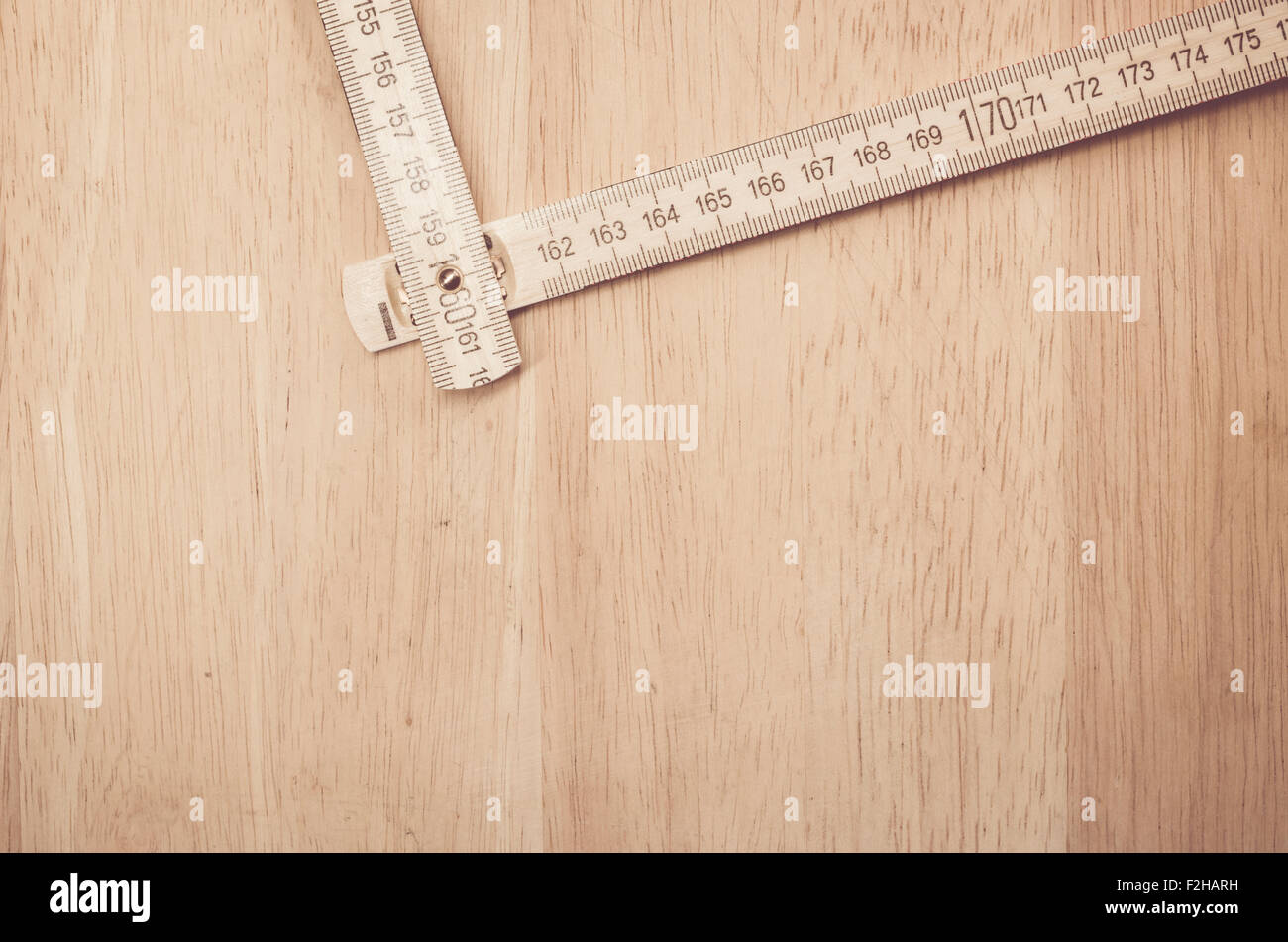 open wood yardstick on a natural wood surface - tools background with copy space - Stock Image
