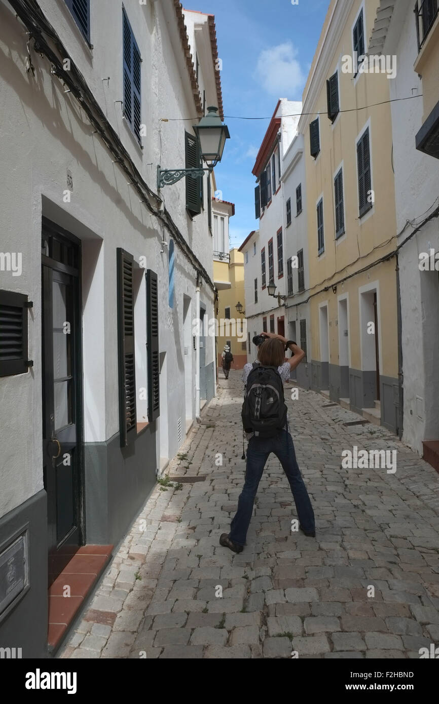 back view of photographer with legs apart taking a picture looking down a narrow street in Menorca, Spain Stock Photo