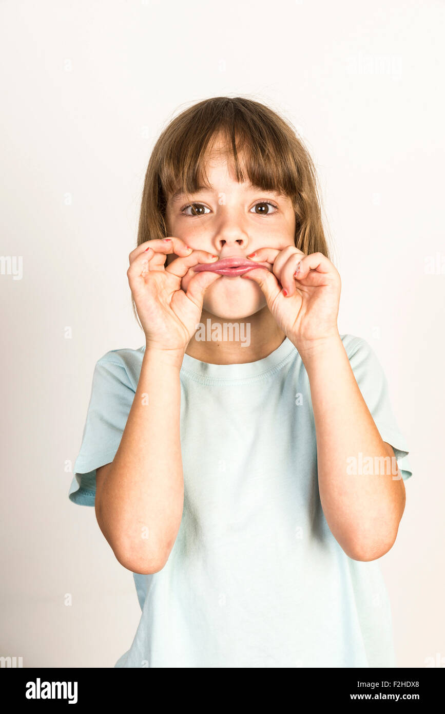 Happy little girl grimacing with fingers clenched lips at home isolated on white background - Stock Image