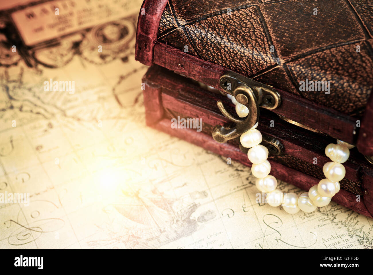 Treasure chest with coins and pearls jewelry over ancient map - Stock Image