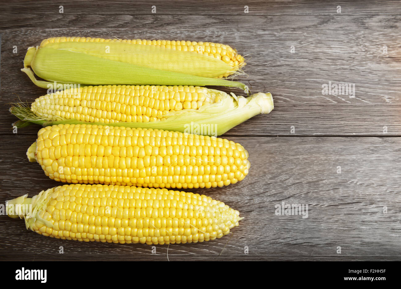 Corn cobs on wooden table - Stock Image